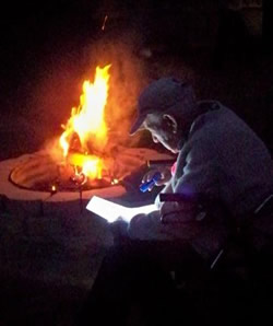 James Hollandsworth reading by a fire