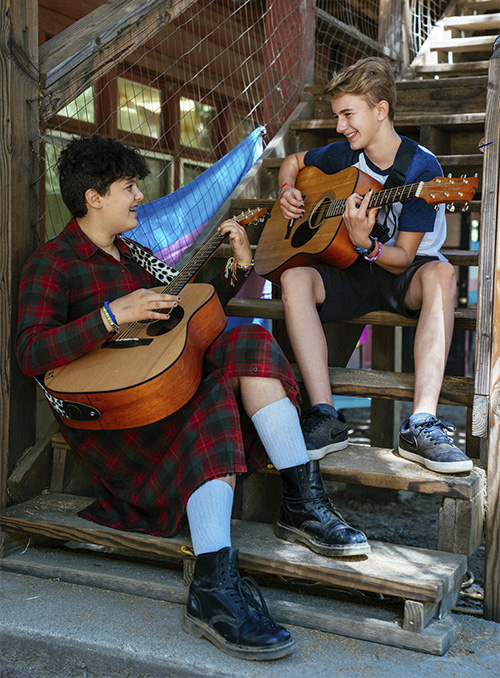 Campers playing guitar on stairs