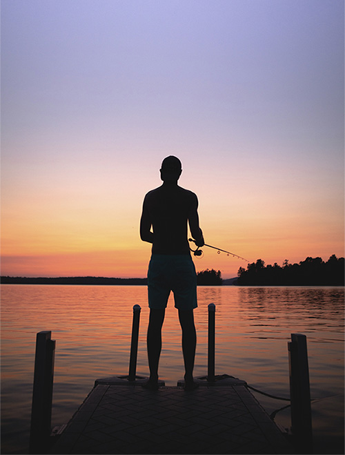 Staffer fishing on dock at sunset