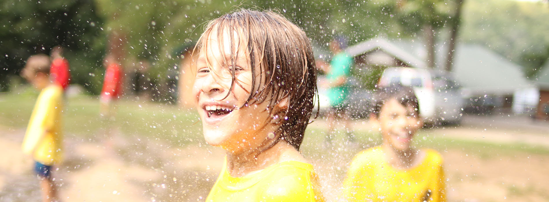 Camper smiling with water droplets falling