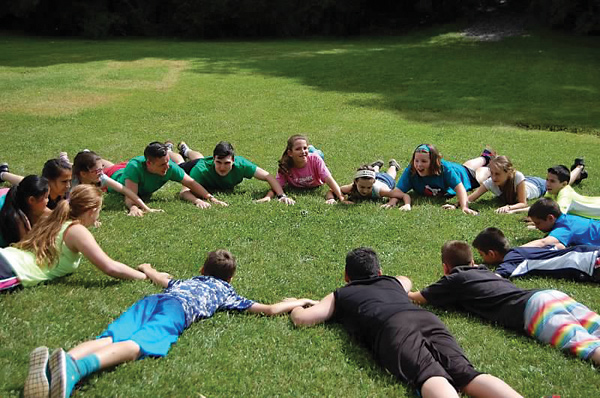 Campers and staff lying in a circle