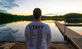 staff member looking over lake at sunrise