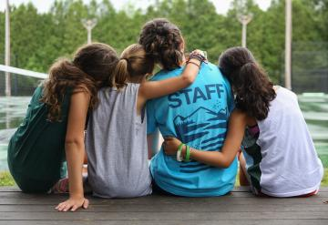 campers with their arms around a camp staff member