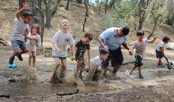 campers and camp stuff jumping in puddles