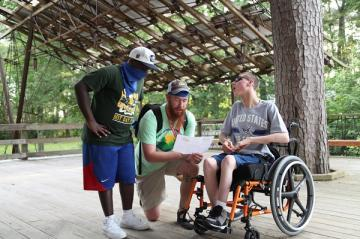 Photo courtesy of MedCamps of Louisiana - staff talking with camper in wheelchair
