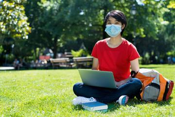 college student wearing mask sitting in grass with laptop