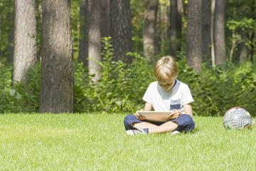 Young boy sitting outside with a tablet