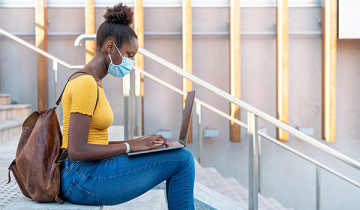 college student wearing mask with laptop