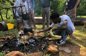 Camper tending to pot cooking over fire