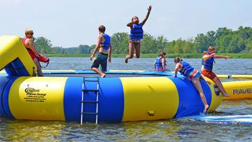 Campers jumping off water trampoline