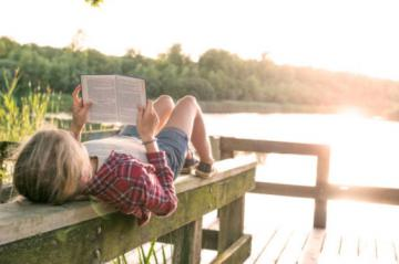 Reading book by lake