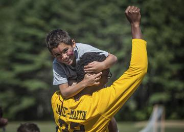 Counselor holding camper with his fist in the air