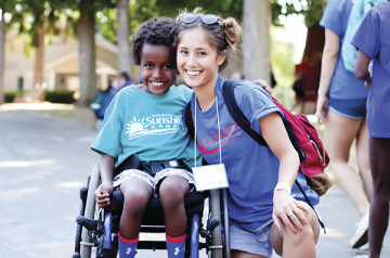 Photo of counselor with camper in wheelchair