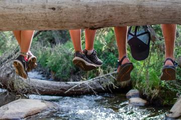 Legs dangling from a log over a stream