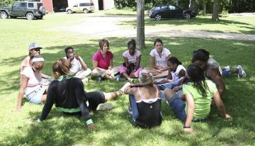 Campers and staff sitting in circle in grass