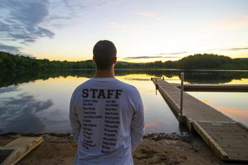 counselor watching sunrise over lake