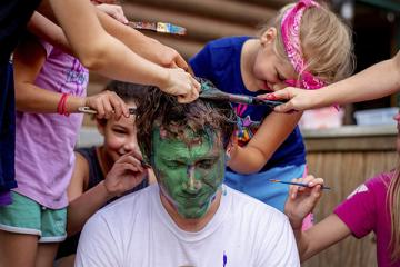 Campers painting face and hair of counselor