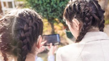 2 girls — one with hearing aid — looking at smartphone
