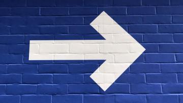 white arrow painted on blue wall