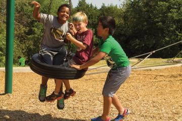Boys playing on tire swing.