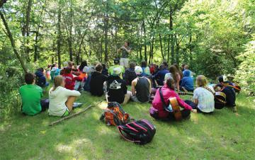 campers sitting outdoors listening to speaker