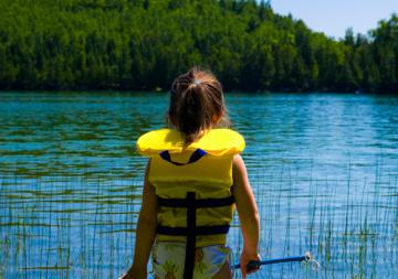 Girl in Lifejacket By Lake