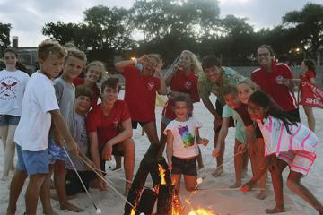 Campers and staff roasting marshmallows