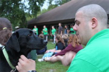 Staff person petting dog - Photo courtesy of Camp Howe, Goshen, MA