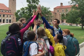 Campers and staff forming a high-five pyramid