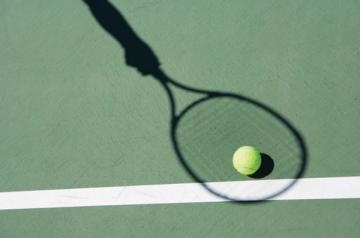 Tennis ball with shadow of racket
